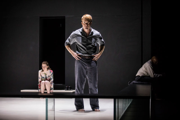 <p>Daniel Abeles stands between Catherine Combs and Ezra Knight, cast in half light.</p><br />(photo provided by the production)