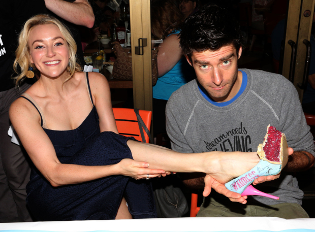 <p>At the autograph table, <em>Waitress</em> stars Betsy Wolfe and Drew Gehling model custom pie-shaped footwear.</p><br />(© David Gordon)