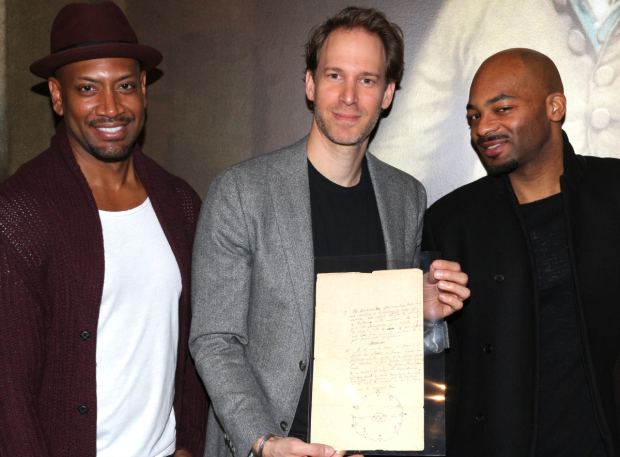 <p>Bryan Terrell Clark (George Washington), David Korins, and Brandon Victor Dixon (Aaron Burr) show off a letter in which Alexander Hamilton lays out the ground plan for his garden.</p><br />(© David Gordon)