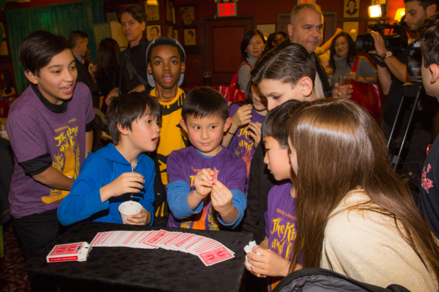 <p>Children from <em>The King and I</em> have fun with some card tricks.</p><br />(© Seth Walters)