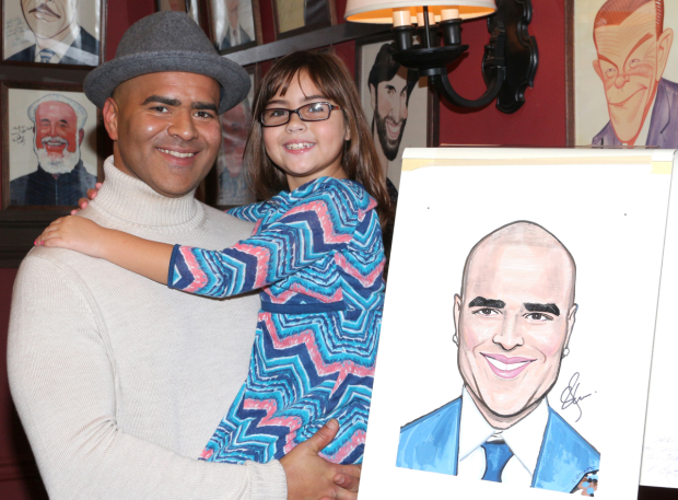 <p>Christopher Jackson and his daughter Jadelyn pose with his new caricature.</p><br />(© David Gordon)