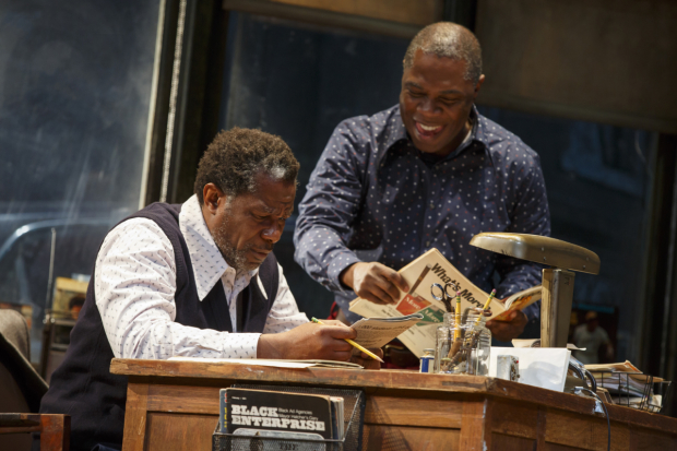 <p>John Douglas Thompson as Becker and Michael Potts as Turnbo peruse periodicals at the office in <em>Jitney</em>.</p><br />(© Joan Marcus)