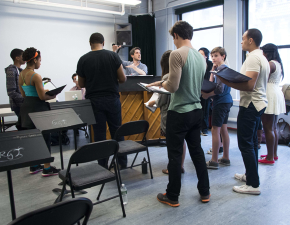 <p>Musical director Bryan Perri works with the young cast around the piano.</p><br />(© Monica Simoes)