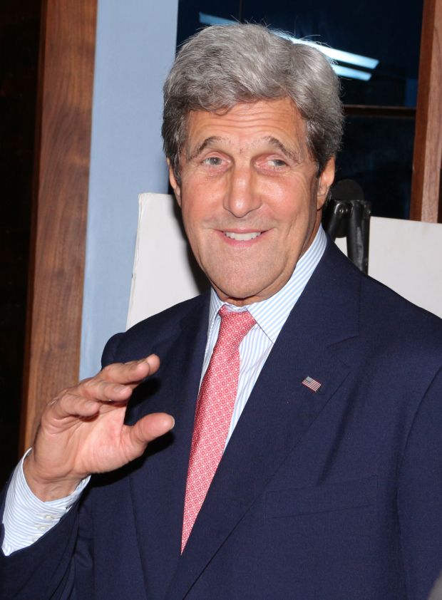 <p>United States Secretary of State John Kerry waves to the photographers.</p><br />(© David Gordon)