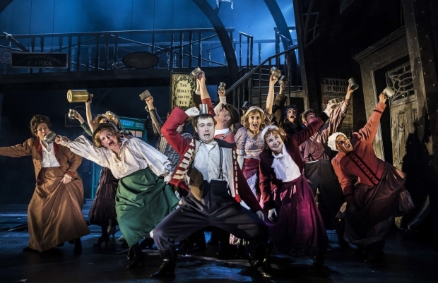 <p>Danny-Boy Hatchard as Tom Jenkins (centre) and the cast of Scrooge the Musical </p><br />© Pamela Raith