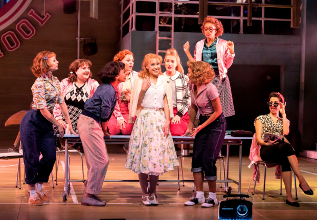 <p>Jessica Paul as Sandy Dumbrowski with the Pink Ladies  in <em>Grease</em> </p><br />© Manuel Harlan